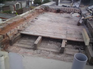 Old, tired flat roof system removed exposing rotted timber structure.